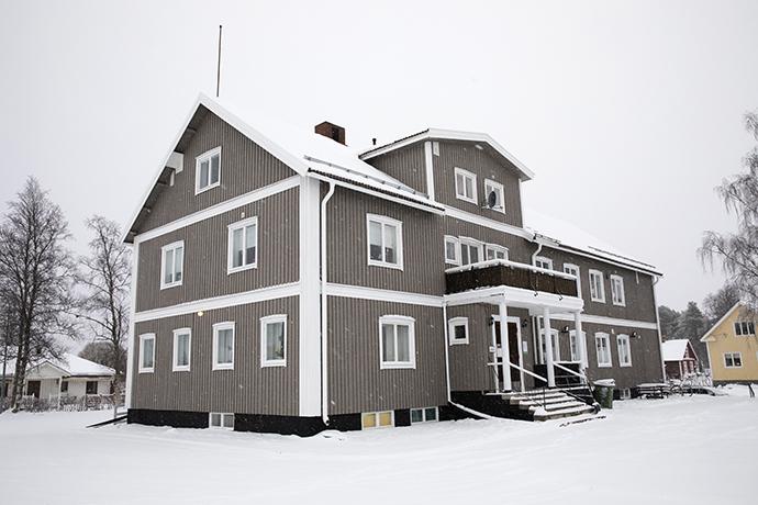 Tvåvåningshus i grå träpanel, snö på marken