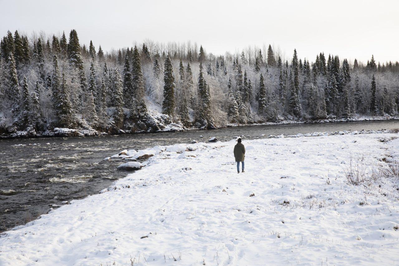En person vandrar vid älvkant i vinterlandskap